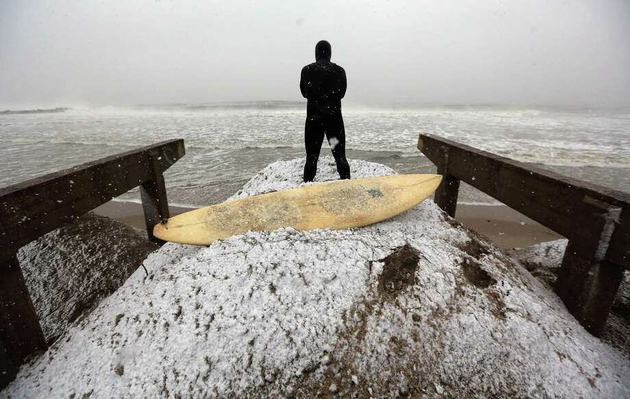 Surfer ''Mandog'' stands on a pile of sand collected from the streets and placed back on the beach amid the destroyed boardwalk as he watches a friend surf while a Nor'Easter approaches in the Rockaway neighborhood on November 7, 2012 in the Queens borough of New York City. The sand is placed back on the beach to clear the streets and also to help prevent possible storm surge. The Rockaway Peninsula was especially hard hit by Superstorm Sandy and some are evacuating ahead to the coming storm. Photo: Mario Tama, Getty Images / 2012 Getty Images