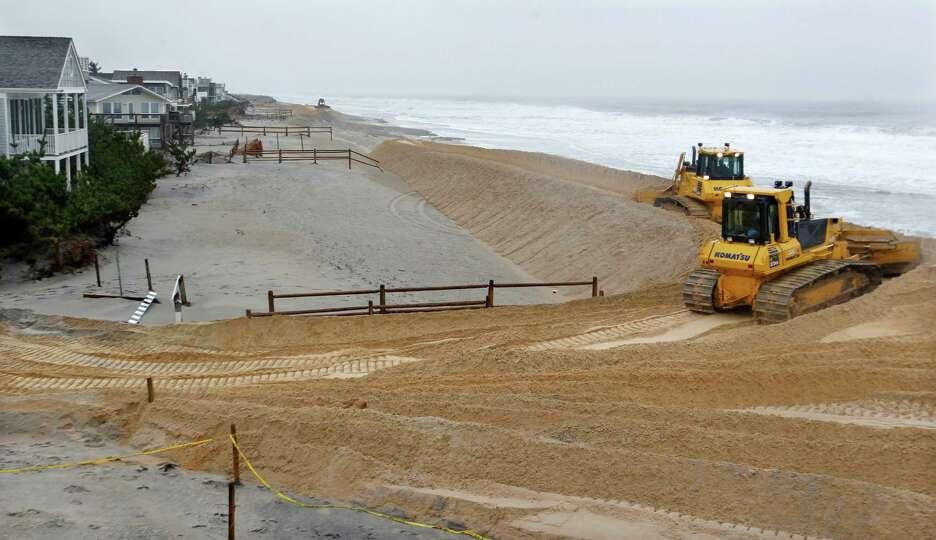 Wokers use heavy machinery spread sand Wednesday, Nov. 7, 2012, in Harvey Cedars, on Long Beach Isla
