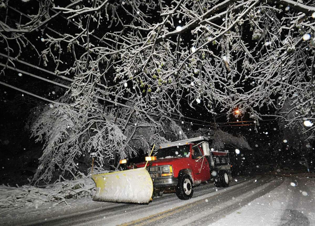 A plow truck makes its way through a snow covered Bruce Park Drive during the nor'easter that hit Greenwich, Wednesday night, November 7, 2012.