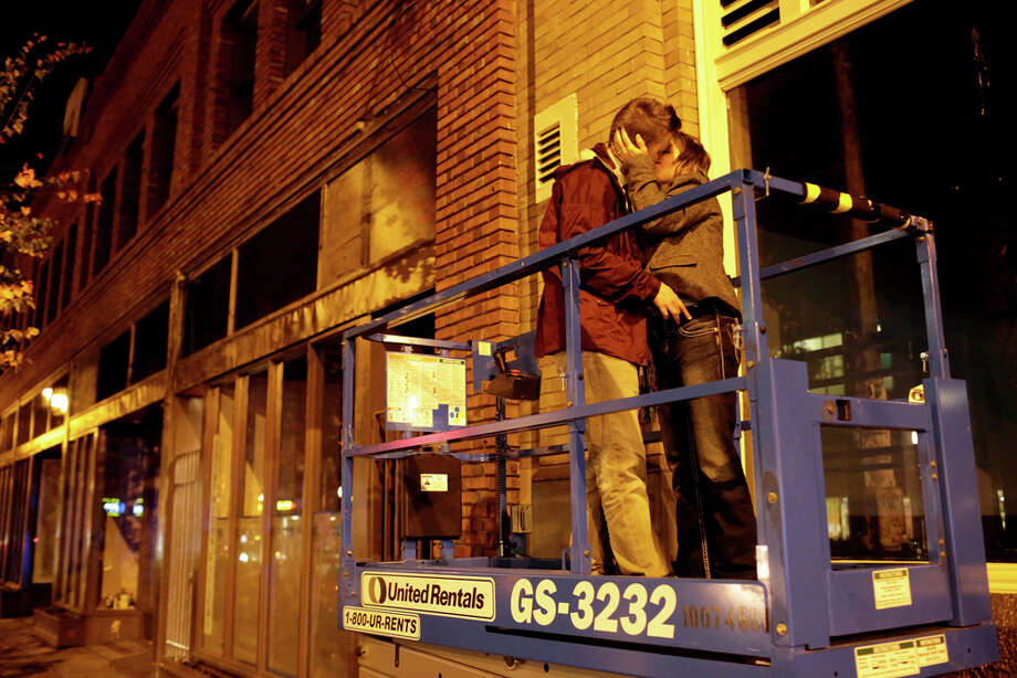 A couple enjoys each other's company on a Genie lift on election night on Tuesday, November 6, 2012, on Capitol Hill in Seattle, Wash. Beforehand, crowds had flocked to return parties hosted by a number of bars in the area to wait out final ballot results. In addition to President Barack Obama's reelection, Referendum 74 and I-502 were both passed in Washington state. Photo: JORDAN STEAD / THE EMERALD COLLECTIVE / FOR SEATTLEPI.COM