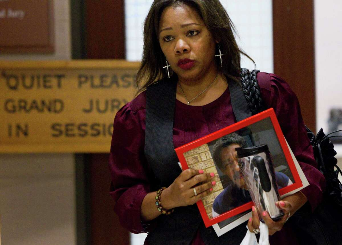 Evangeline Campbell leaves the Harris County Grand Jury carrying a photo of her late father, Norman Ford Hicks, Wednesday, Sept. 14, 2011, in Houston. A grand jury decided Wednesday that criminal charges are not warranted in the January death of the 72-year-old Hicks after an altercation in the Harris County jail, the district attorney's office confirmed. ( Brett Coomer / Houston Chronicle )