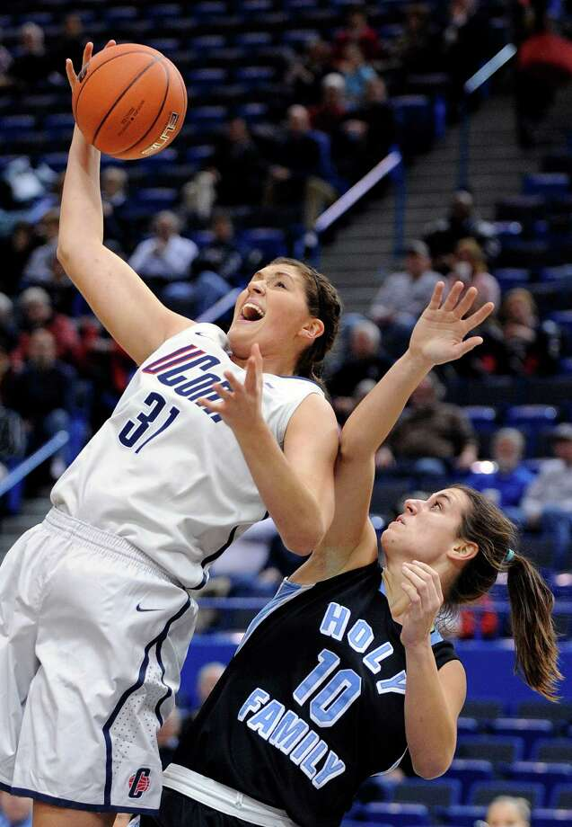 Connecticut's Stefanie Dolson, left, grabs a rebound from Holy Family's Kelly Brady during the first half of an exhibition NCAA college basketball game in Hartford, Conn., on Wednesday, Nov. 7, 2012. (AP Photo/Fred Beckham) Photo: Fred Beckham, Associated Press / FR153656 AP