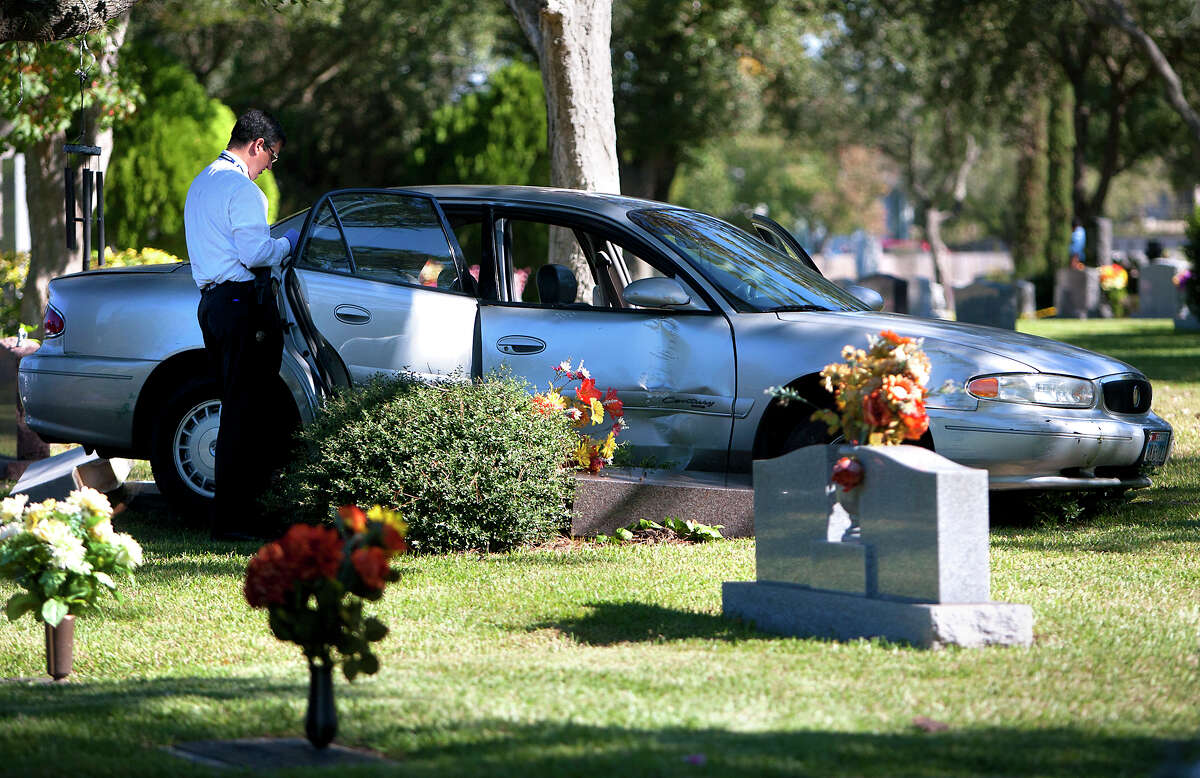 Investigators work the scene after a police chase for three suspected bank robbers ended at Forest Park Westheimer Cemetery.