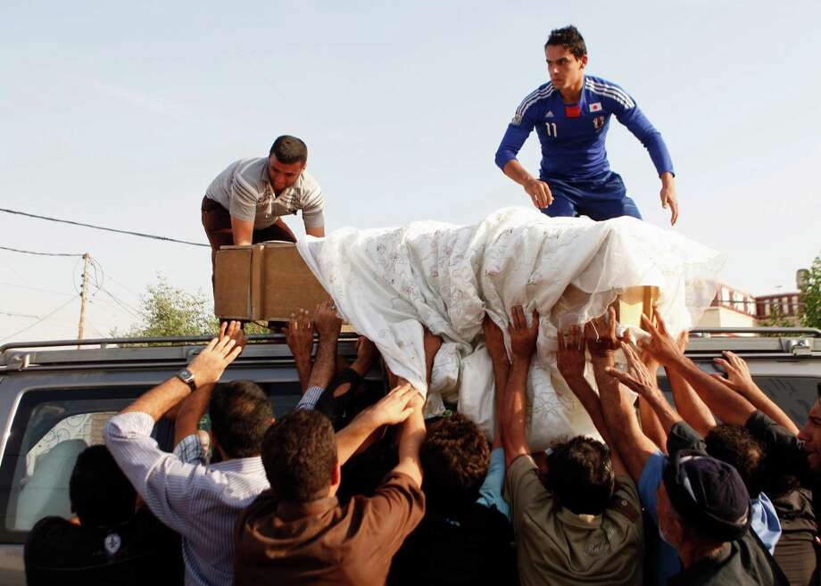 Relatives and friends of Ali Dhia Abbas, 25, load his coffin onto a vehicle during his funeral in Baghdad, Iraq, Wednesday, Nov. 7, 2012. Abbas was killed when a suicide bomber driving a car packed with explosives detonated the vehicle near an Iraqi military base as soldiers changed shifts north of Baghdad on Tuesday, killing and injuring dozens of Iraqis, police said. (AP Photo/Karim Kadim) Photo: Karim Kadim