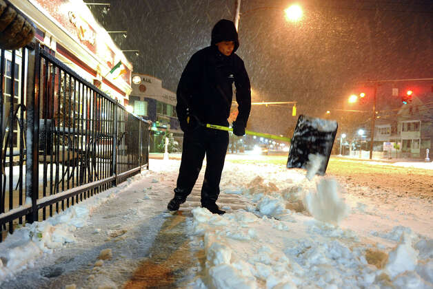 Employee Luis Ramos shovels snow off the sidewalk in front of The Field restaurant in the Black Rock section of Bridgeport, Conn. on Wednesday November 7, 2012. Photo: Christian Abraham / Connecticut Post