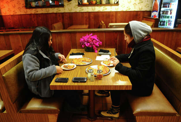 To get out of the cold and snow, Maryrose Julian, left, and her friend Andrea Bazan enjoy some pizza after work at Beverly Pizza in the Black Rock section of Bridgeport, Conn. on Wednesday November 7, 2012. Photo: Christian Abraham / Connecticut Post