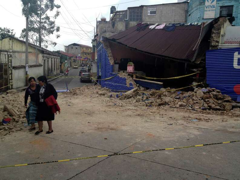 Two women walk past a building damaged after a magnitude 7.4 earthquake struck in San Marcos, Guatem