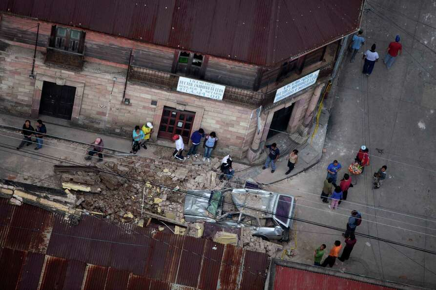 Residents walk around rubble and a car damaged after a magnitude 7.4 earthquake struck in San Marcos