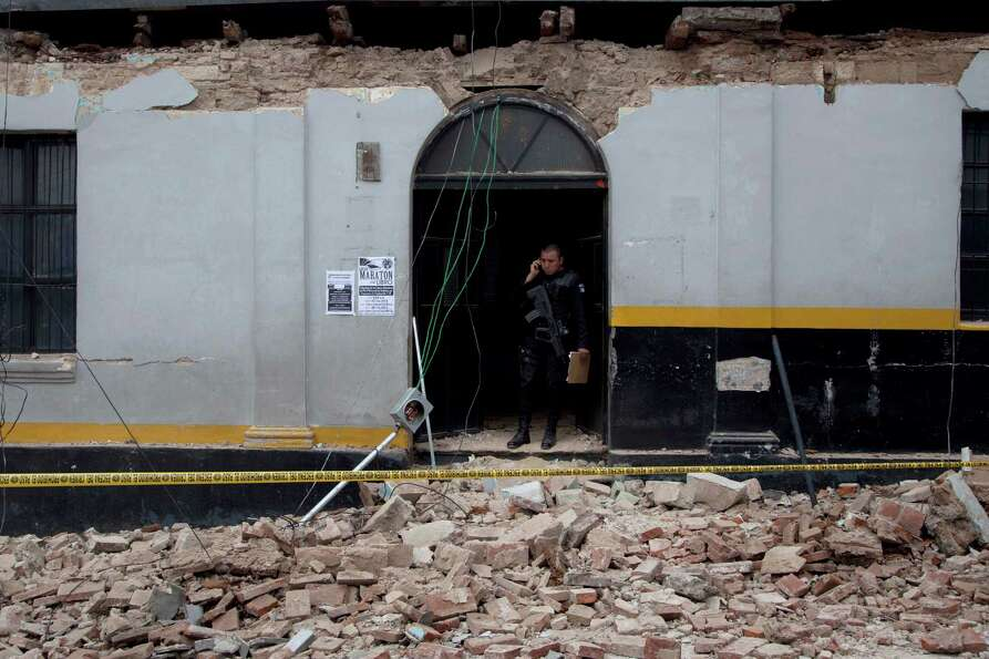 A  police officer stands in the archway of a building damaged by a magnitude 7.4 earthquake that str