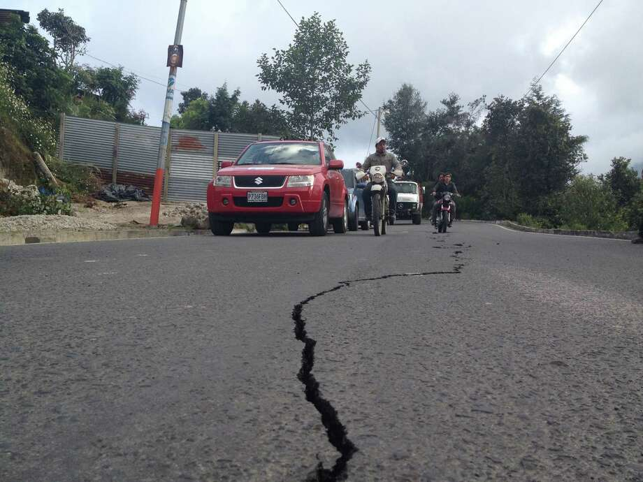 Residents on motorcycles drive past a damaged road after a magnitude 7.4 earthquake struck in San Marcos, Guatemala, Wednesday, Nov. 7, 2012. The mountain village, some 80 miles (130 kilometers) from the epicenter, suffered much of the damage with some 30 homes collapsing in its center. There are three confirmed dead and many missing after the strongest earthquake to hit Guatemala since a deadly 1976 quake that killed 23,000. (AP Photo/Moises Castillo) Photo: Moises Castillo