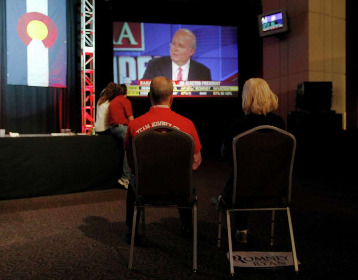 Fox News commentator Karl Rove chides his fellow Fox analysts on a big-screen television during a Republican Party election night gathering in Denver.