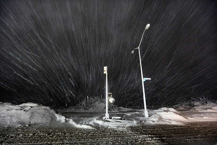 Snow blows past debris and nonfunctioning streetlights during a Nor'Easter snowstorm on November 7, 2012 in the Rockaway neighborhood of the Queens borough of New York City. The Rockaway Peninsula was especially hard hit by Superstorm Sandy and some are evacuating ahead of the coming storm. Photo: Mario Tama, Getty Images