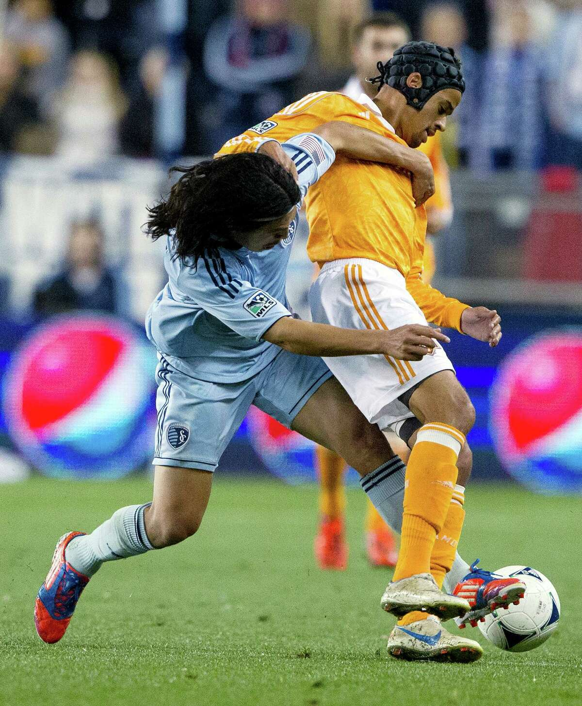 Sporting KC midfielder Roger Espinoza (15) wraps himself around Houston Dynamo forward Calen Carr (3) in the first half during Wednesday's MLS playoff soccer game on November 7, 2012, at Livestrong Sporting Park in Kansas City, Ks. John Sleezer/The Kansas City Star