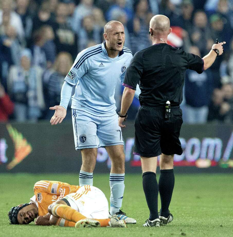 Sporting KC defender Aurelien Collin (78) tries to plead his case as Houston Dynamo forward Calen Carr (3) rolls on the ground in the first half during Wednesday's MLS playoff soccer game on November 7, 2012, at Livestrong Sporting Park in Kansas City, Ks. John Sleezer/The Kansas City Star Photo: JOHN SLEEZER, The Kansas City Star