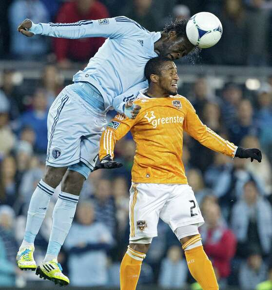 Sporting KC forward Kei Kamara (23) heads the ball over Houston Dynamo midfielder Corey Ashe (26) in