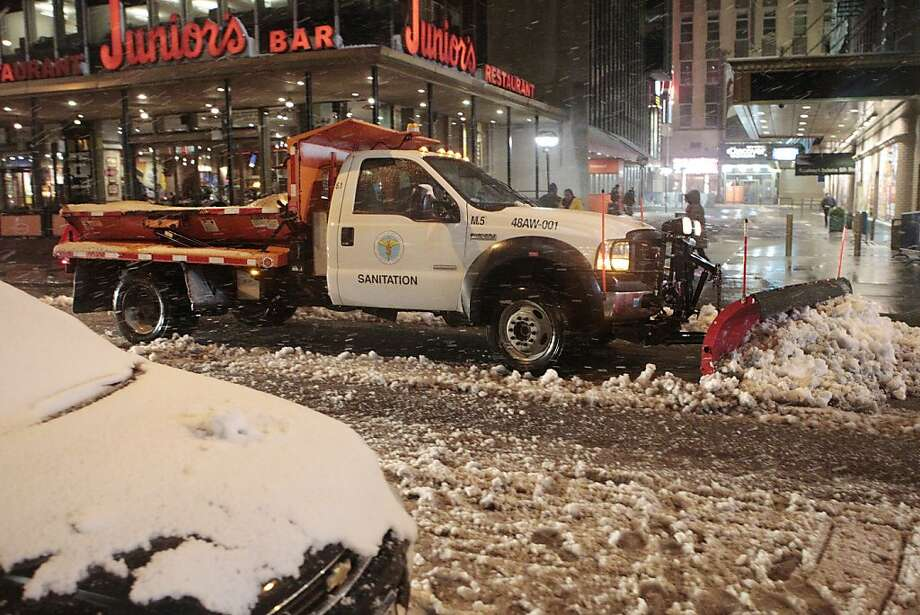 Sanitation workers shovel snow from the streets of Times Square Wednesday, Nov. 7, 2012, in New York. Coastal residents of New York and New Jersey faced new warnings to evacuate their homes and airlines canceled hundreds of flights as a new storm arrived Wednesday, only a week after Superstorm Sandy left dozens dead and millions without power. (AP Photo/Frank Franklin II) Photo: Frank Franklin II, Associated Press