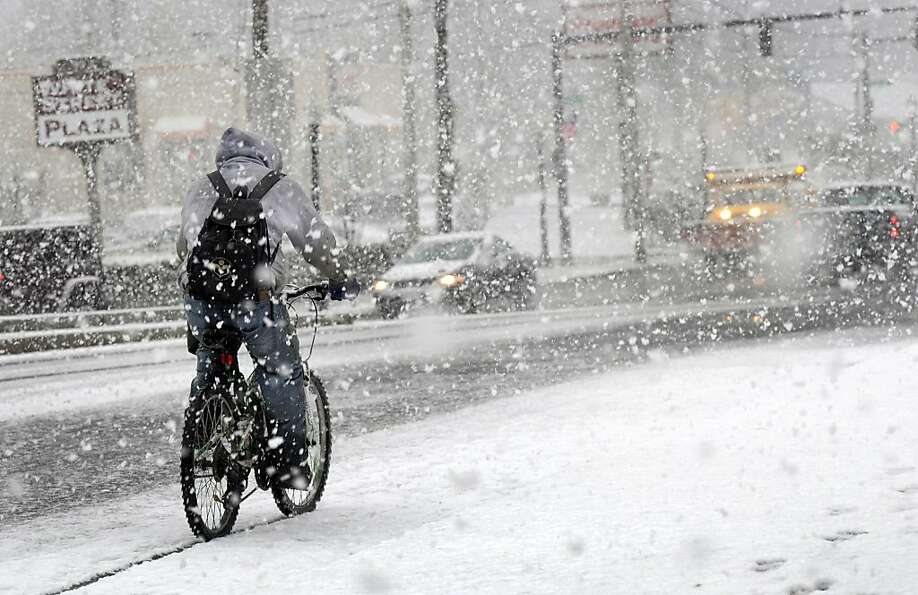 A bicyclist rides in the snow down White Street in Danbury Wednesday afternoon, Nov. 7, 2012.