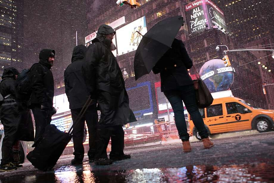 Pedestrians walk through Times Square as it snows Wednesday, Nov. 7, 2012, in New York. Coastal residents of New York and New Jersey faced new warnings to evacuate their homes and airlines canceled hundreds of flights as a new storm arrived Wednesday, only a week after Superstorm Sandy left dozens dead and millions without power. (AP Photo/Frank Franklin II) Photo: Frank Franklin II, Associated Press