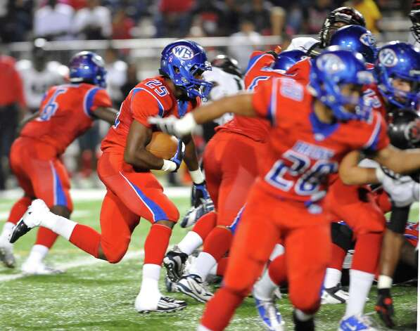 "West Brook Bruin #25, Justin Hervey, left, heads for a hole that his teammates opened up for him to run through. The West Brook Bruins hosted the Port Arthur Memorial Titans football team Friday night at the Carrol A.""Butch"" Thomas Educational Support Center Beaumont.  This was a District 21-5A game. At the half, the score was the Titans 35, the Bruins 10.  Dave Ryan/The Enterprise Photo: Dave Ryan"