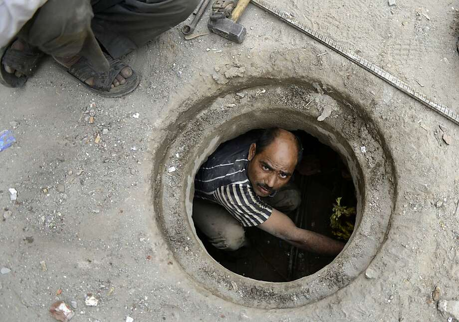Indian plumber Jaipal looks up as he fixes an underground water pipe in New Delhi on November 7, 2012.  Jaipal, an immigrant labourer who left his home in Jhansi in Uttar Pradesh state 13 years ago to work and settle in Delhi, earns INR 300 per day.  Every year scores of poor workers come to Delhi in search of better employment opportunities. Photo: Sajjad Hussain, AFP/Getty Images
