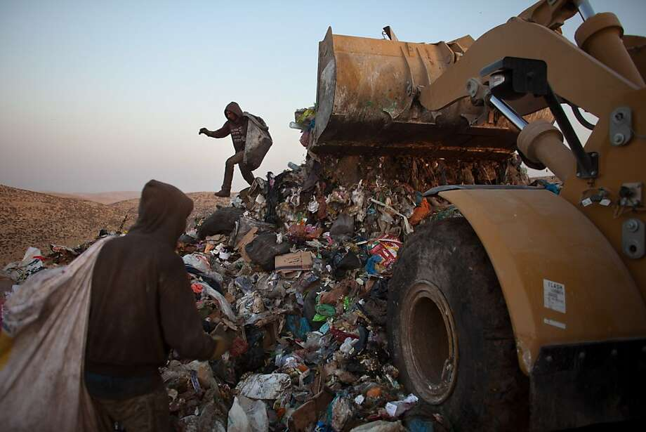 Palestinian children sift through a garbage dump on November 7, 2012 south of Hebron, West Bank. About 40 Palestinain men and children work at the West Bank garbage dump looking for clothing, metal and wood discarded, in large part, from the Jewish settelment in the region. Photo: Uriel Sinai, Getty Images