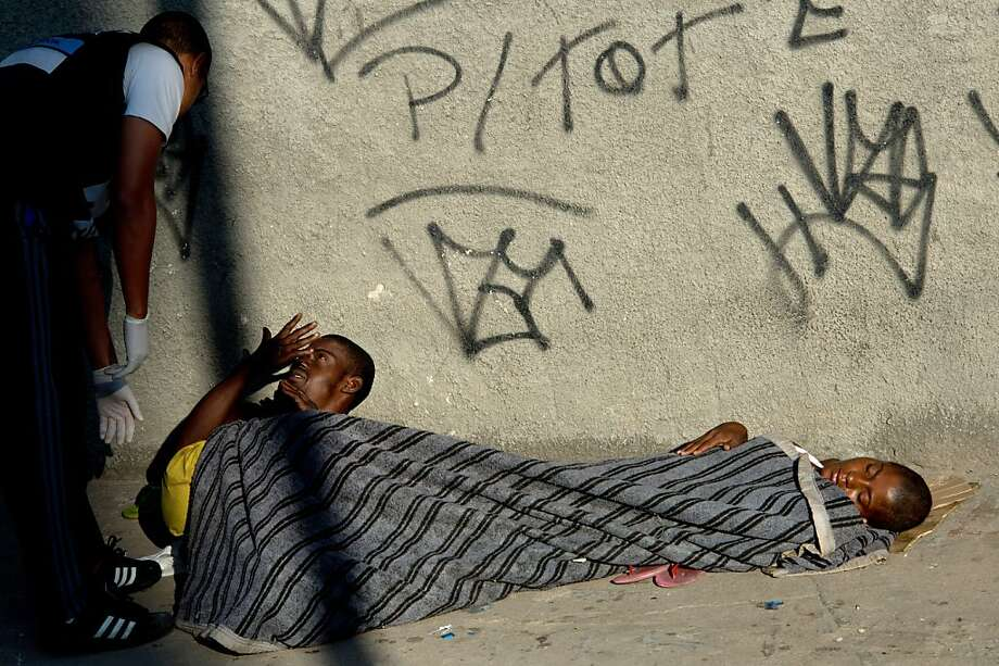 A social worker wakes up a crack addict who was sleeping on the ground in the vicinity of Parque Uniao slum during a municipal social workers and police joint operation to take addicts out of the streets, in Rio de Janeiro, Brazil on November 7, 2012. Photo: Christophe Simon, AFP/Getty Images