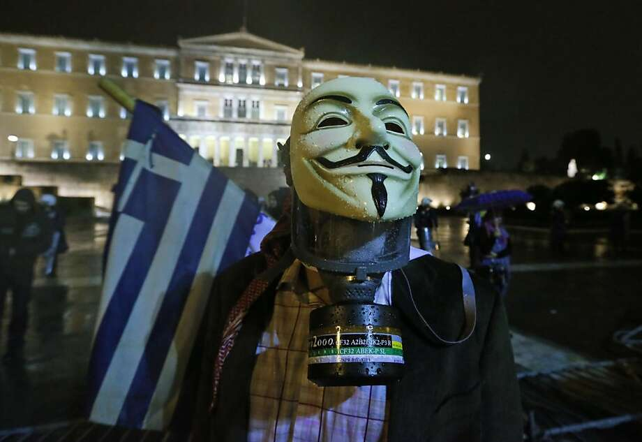 A protester is seen outside the parliament in Athens, Wednesday Nov. 7, 2012. Greece's fragile coalition government faces its toughest test so far when lawmakers vote later Wednesday on new painful austerity measures demanded to keep the country afloat, on the second day of a nationwide general strike. The euro13.5 billion ($17.3 billion) package is expected to scrape through Parliament, following a hasty one-day debate. Photo: Lefteris Pitarakis, Associated Press