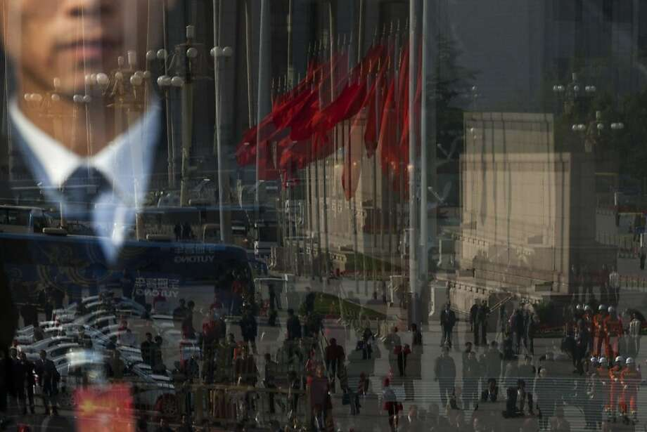 Journalists, firemen, buses, and red flags on Tiananmen are reflected in a glass door of the Great Hall of the People, where opening ceremony of the 18th Communist Party Congress is held, while a soldier dressed as an usher, seen through the glass, keeps watching in Beijing, Thursday, Nov. 8, 2012. China's ruling Communist Party opened a congress Thursday to usher in a new group of younger leaders faced with the challenging tasks of righting a flagging economy and meeting public calls for better government. (AP Photo/Alexander F. Yuan) Photo: Alexander F. Yuan, Associated Press
