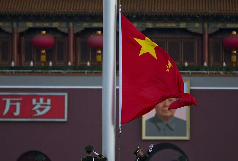 "Paramilitary policemen salute while a Chinese national flag is raised at sunrise on Tiananmen Square, facing Tiananmen Gate with Chinese characters that reads ""Long Live"", before the 18th Communist Party Congress is held at the nearby Great Hall of the People in Beijing, China, Thursday, Nov. 8, 2012. China's ruling Communist Party opened a congress Thursday to usher in a new group of younger leaders faced with the challenging tasks of righting a flagging economy and meeting public calls for better government. (AP Photo/Alexander F. Yuan) Photo: Alexander F. Yuan, Associated Press"