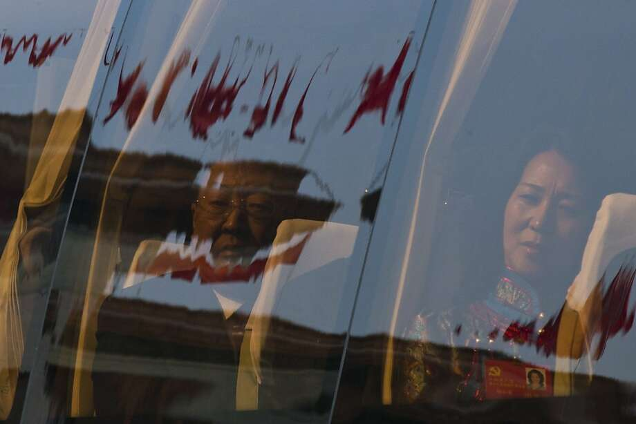 Chinese Communist Party delegates sit on a bus to leave the Great Hall of the People after opening session of the 18th Communist Party Congress, while red flags are reflected in the bus window in Beijing, China, Thursday, Nov. 8, 2012. Preparing to hand over power after a decade in office, China's President Hu Jintao called Thursday for sterner measures to combat official corruption that has stoked public anger while urging the Communist Party to maintain firm political control. (AP Photo/Alexander F. Yuan) Photo: Alexander F. Yuan, Associated Press