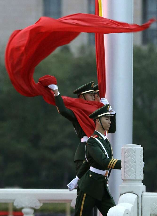 A Chinese paramilitary policeman tries to grab a flag at Tiananmen Square in Beijing, China, Wednesday, Nov. 7, 2012. The Chinese Communist Party's 18th National Congress is scheduled to begin Nov. 8 in the Chinese capital. The once-a-decade event installs a new leadership to run the world's second largest economy and newly assertive global power. (AP Photo/Lee Jin-man) Photo: Lee Jin-man, Associated Press