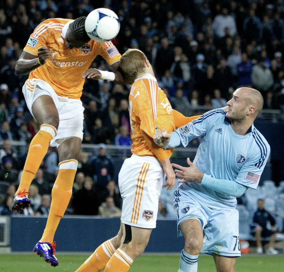 Houston Dynamo forward Macoumba Kandji (9) clears the ball from in front of the net with a header over teammate Andre Hainault (31) and Sporting KC defender Aurelien Collin (78) in the closing minutes of the second half during Wednesday's MLS playoff soccer game on November 7, 2012, at Livestrong Sporting Park in Kansas City, Ks. John Sleezer/The Kansas City Star Photo: JOHN SLEEZER, The Kansas City Star