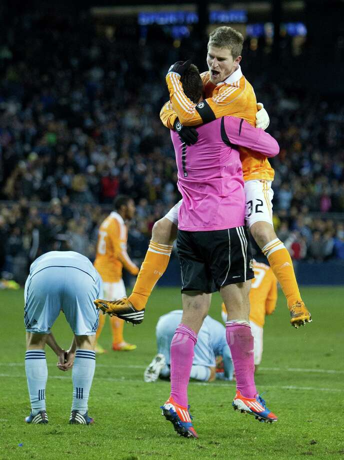 Houston Dynamo defender Bobby Boswell (32) leaps into the arms of goalkeeper Tally Hall (1) after defeating Sporting KC in aggregate scoring to advance in the playoffs during Wednesday's MLS playoff soccer game on November 7, 2012, at Livestrong Sporting Park in Kansas City, Ks. John Sleezer/The Kansas City Star Photo: JOHN SLEEZER, The Kansas City Star