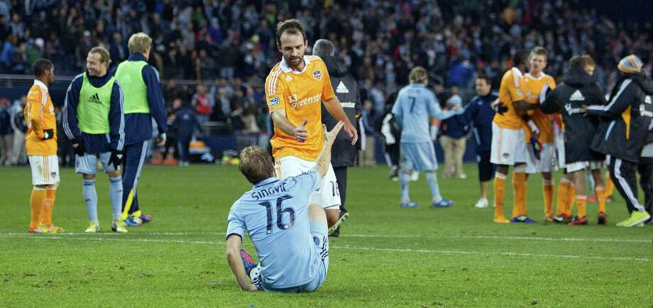 Sporting KC defender Seth Sinovic (16) is helped up by Houston Dynamo midfielder Adam Moffat (16) after Sporting lost to the Dynamo's in aggregate scoring during Wednesday's MLS playoff soccer game on November 7, 2012, at Livestrong Sporting Park in Kansas City, Ks. Houston Dynamo advanced in the playoffs as Sporting KC ended their season. John Sleezer/The Kansas City Star Photo: JOHN SLEEZER, The Kansas City Star