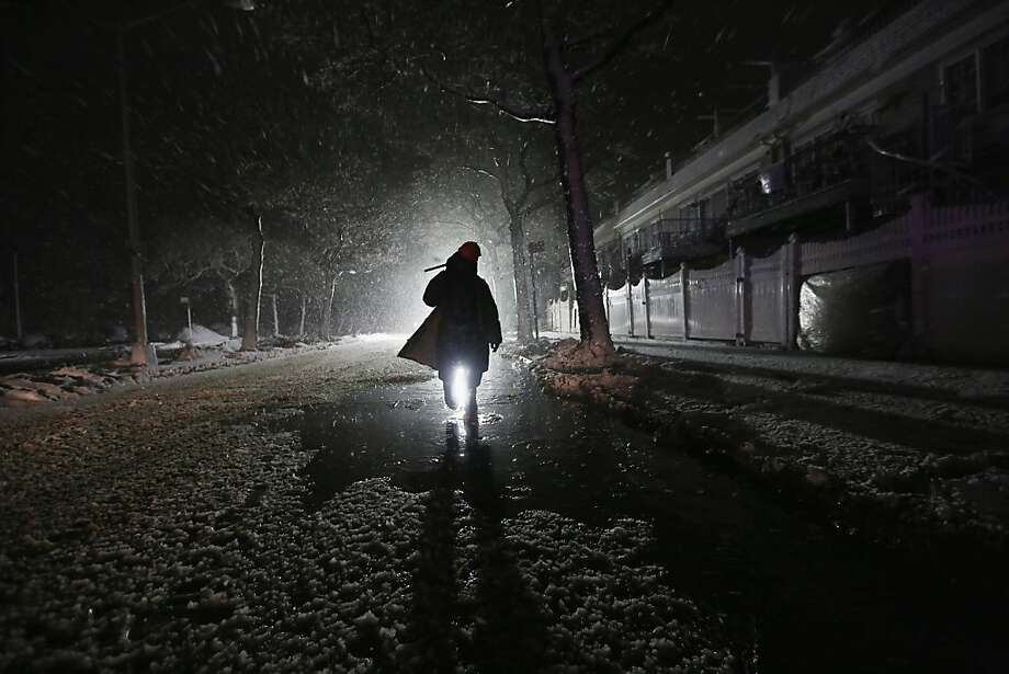 NEW YORK, NY - NOVEMBER 07:  A repair worker is silhouetted by a police spotlight as he walks down a darkened street during a Nor'Easter snowstorm on November 7, 2012 in the Rockaway neighborhood of the Queens borough of New York City. The Rockaway Peninsula was especially hard hit by Superstorm Sandy and some are evacuating ahead of the coming storm. (Photo by Mario Tama/Getty Images) ***BESTPIX*** Photo: Mario Tama, Getty Images
