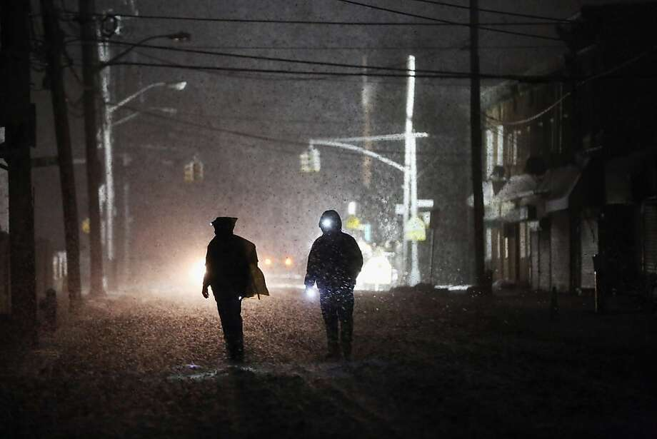 NEW YORK, NY - NOVEMBER 07:  People walk through a darkened street using flashlights as a police spotlight shines behind them during a Nor'Easter snowstorm in the Rockaway neighborhood on November 7, 2012 in the Queens borough of New York City. The Rockaway Peninsula was especially hard hit by Superstorm Sandy and some are evacuating ahead of the coming storm.   (Photo by Mario Tama/Getty Images) Photo: Mario Tama, Getty Images