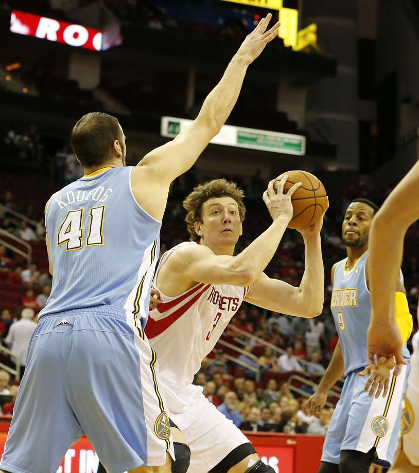 The Rockets Omer Asik center, shoots the ball between the Nuggets Kosta Koufos left, and Andre Iguodala.    (James Nielsen / Houston Chronicle)
