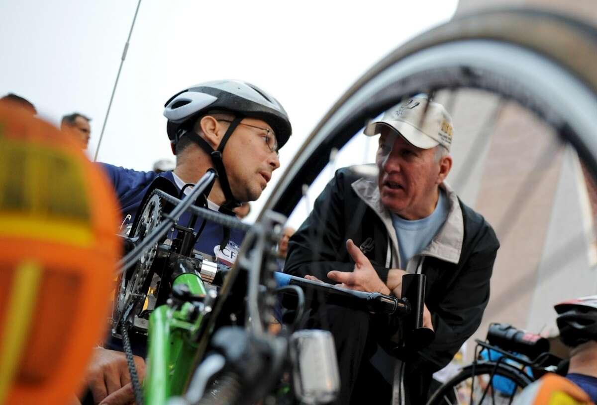 Spurs coach Gregg Popovich (right) talks with Ivan Valentin (left) in his modified wheelchair at the start of the San Antonio Rock 'n' Roll Marathon and Half Marathon on Nov. 13, 2011. (San Antonio Express-News)