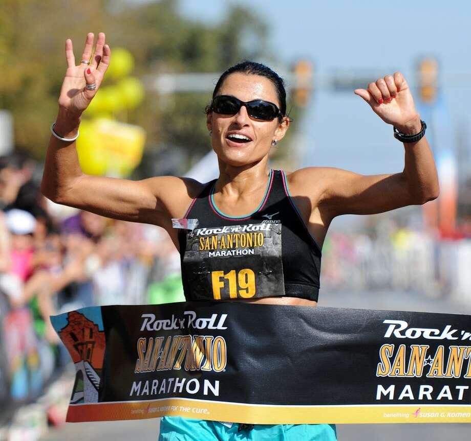 Liza Hunter-Galvan crosses the finish line in the San Antonio Rock 'n' Roll Marathon on Nov. 13, 2011. (San Antonio Express-News)