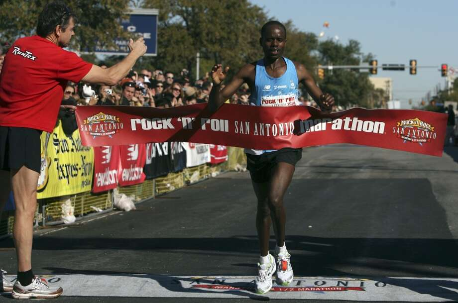 Meschack Kirwa of Kenya crosses the finish line to win the Rock 'n' Roll San Antonio Marathon. Kirwa's time was 2:14:38. On the left in the red shirt is Texas Governor Rick Perry. (SAN ANTONIO EXPRESS-NEWS)