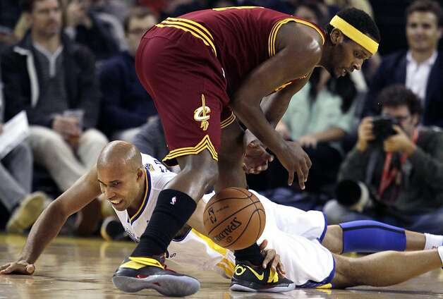 Golden State Warriors forward Richard Jefferson, bottom, reaches for the ball under Cleveland Cavaliers forward C.J. Miles during the first quarter of an NBA basketball game in Oakland, Calif., Wednesday, Nov. 7, 2012. (AP Photo/Jeff Chiu) Photo: Jeff Chiu, Associated Press