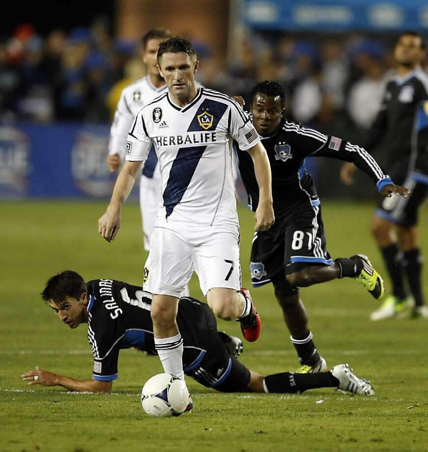 Robbie Keane moves the dribbles the ball up the field in the second period past several Earthquakes. The LA Galaxy defeated the San Jose Earthquakes in the 2012 MLS Cup Playoffs at Buck Shaw Stadium in Santa Clara, Calif., on Wednesday, November 7, 2012. Photo: Carlos Avila Gonzalez, The Chronicle