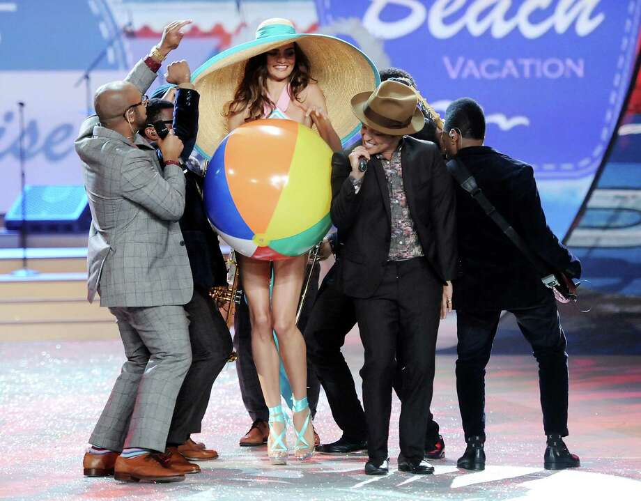 Singer Bruno Mars, center, performs while a model walks the runway. Photo: Evan Agostini /Invision/AP
