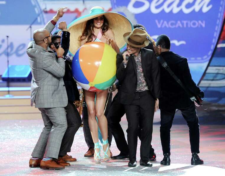 Singer Bruno Mars, center, performs while a model walks the runway.
