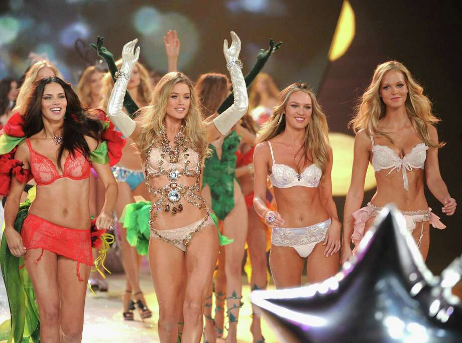 From left, Victoria's Secret Angels Adriana Lima, Doutzen Kroes, Candice Swanepoel, and Erin Heatherton walk the runway. Photo: Jamie McCarthy, Getty Images / 2012 Getty Images