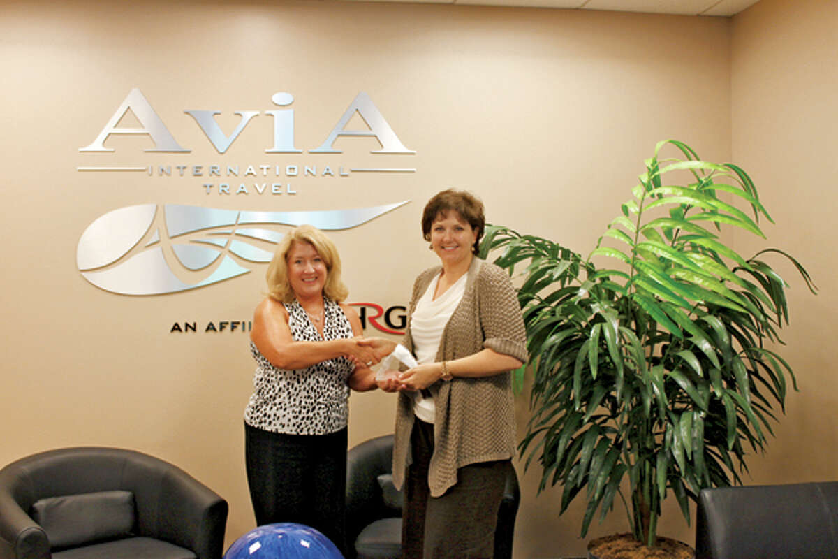 Leigh Dillhoff, left, Sabre Holdings' business development manager, presents Antonella Ballatori, Avia International Travel/HRG's president, with the Peak of Excellence award for 2012.
