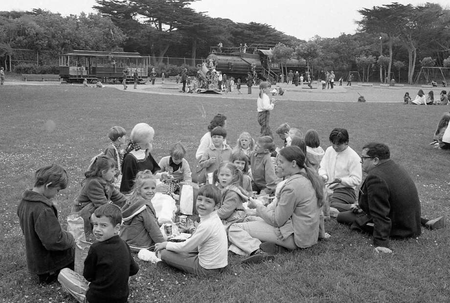 May 22, 1972: Students eat lunch on the lawn near the playground at the San Francisco Zoo. The locomotive and cable car play structures are in the distance. Photo: Joseph J. Rosenthal, The Chronicle / ONLINE_YES