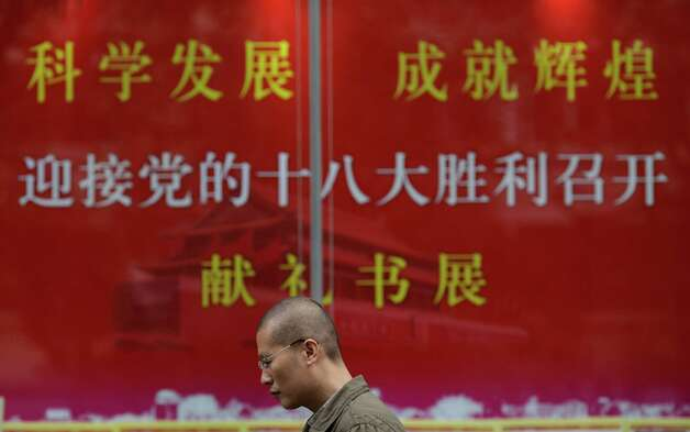 A man walks past an official propaganda to welcome the Chinese Communist Party's 18th Congress which held in Beijing, at a bookstore in Shanghai, China, Thursday Nov. 8, 2012. China's ruling Communist Party opened a congress Thursday to usher in a new group of younger leaders faced with the challenging tasks of righting a flagging economy and meeting public calls for better government. (AP Photo/Eugene Hoshiko) Photo: Eugene Hoshiko