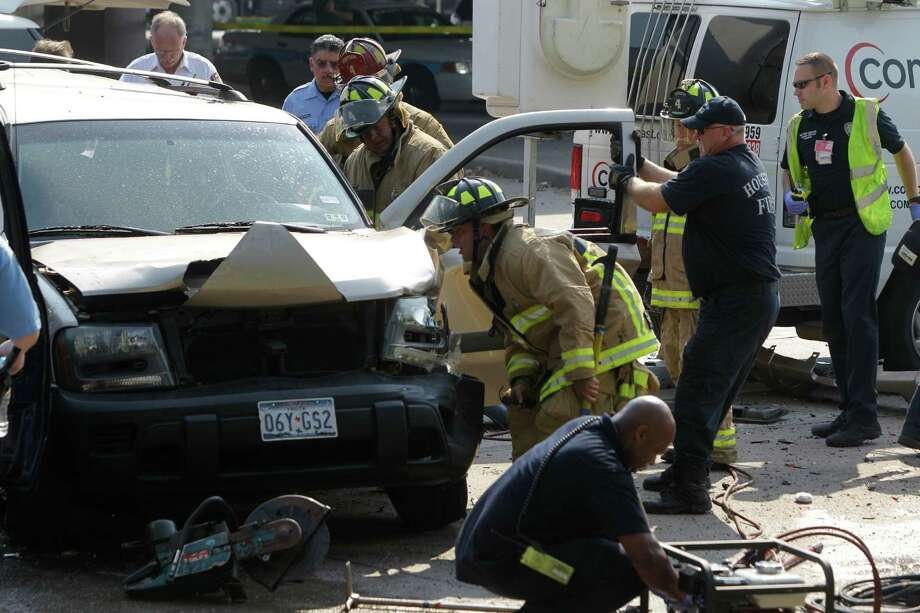 Houston firefighters work to remove two people trapped inside a SUV after a Chevrolet Trailblazer driven by a fleeing shooting suspect crashed into the SUV and several other vehicles during a police chase along the inbound feeder of 290 at Hollister Wednesday, June 27, 2012, in Houston.   Houston police say the suspect died at the scene but it was unclear if he was fatally shot by the officers or died from his injuries after the car wreck. Photo: Melissa Phillip, Houston Chronicle / © 2012 Houston Chronicle