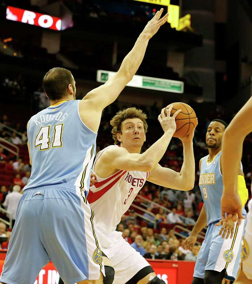 The Houston Rockets Omer Asik center, shoots the ball between the Denver Nuggets Kosta Koufos left, and Andre Iguodala right during the first quarter of NBA game action at the Toyota Center Wednesday, Nov. 7, 2012, in Houston. Photo: James Nielsen, Chronicle / © Houston Chronicle 2012